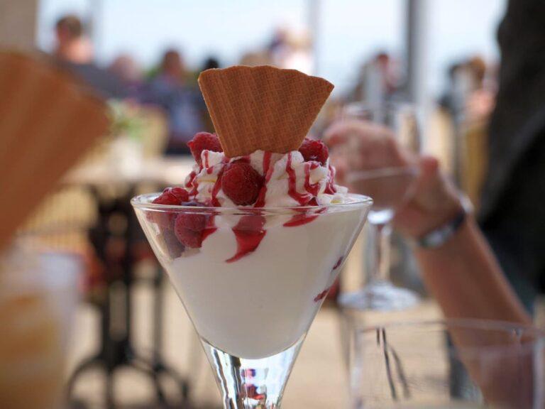Postre helado de yogur con sirope de fresas