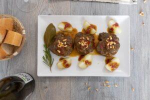 Carrilleras al horno con piñones y patatas